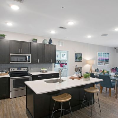 Interior image of apartment kitchen, island, wood floors, dark wood cabinets and stainless steel appliances